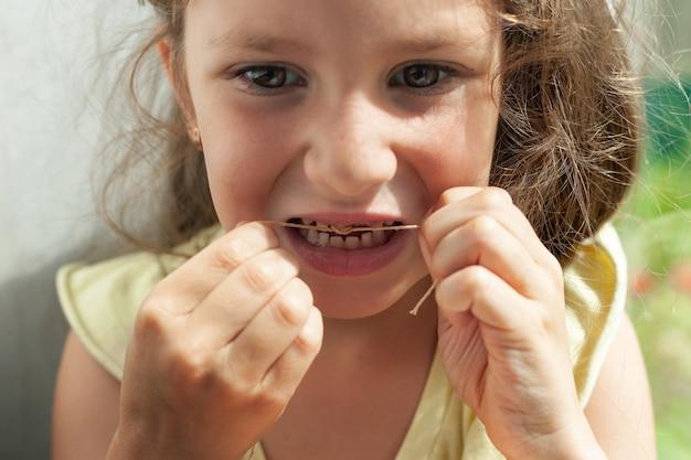 Een meisje van zes jaar bond een draad aan een tand en probeert een tand eruit te trekken