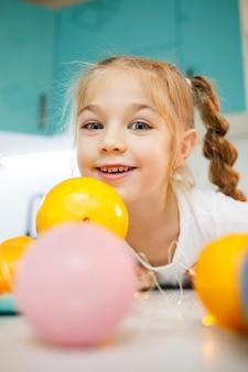 Een meisje van zeven jaar draagt een wit t-shirt. speelt met rijpe mandarijnen