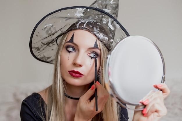 Een meisje verkleed als heks maakt voor zichzelf een halloween-make-up
