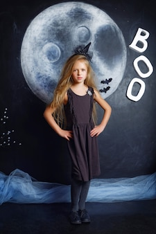 Een meisje verkleedde zich als een heks met halloween-versieringen