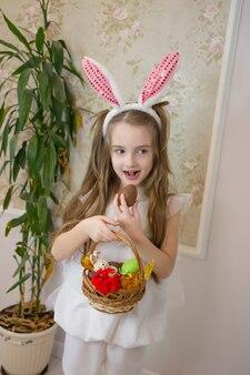 Een meisje verkleedde zich als paashaas met een mand met chocolade-eieren