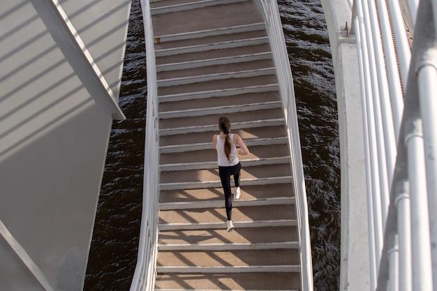 Een meisje verlicht door de zon rent de trap op