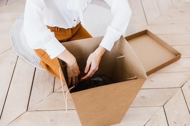 Een meisje verpakt een geschenk in een mooie grote knutselkist, een geschenk voor haar moeder, een collega, een vriend, een ongewone verrassing, bezorging van goederen bij u thuis of op kantoor