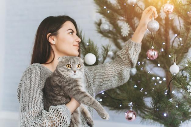 Een meisje versiert een kerstboom en speelt met haar kat.