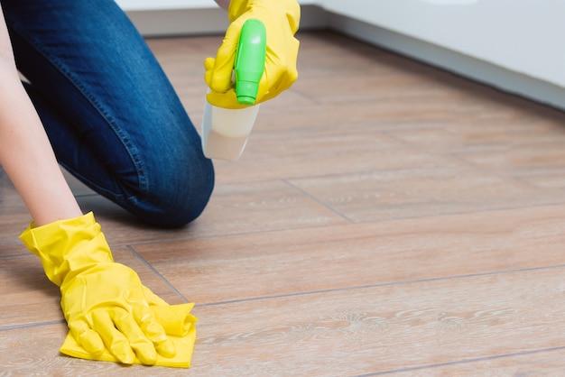 Een meisje wast een vloer in gele handschoenen. een meisje maakt een kamer schoon met wasmiddelen