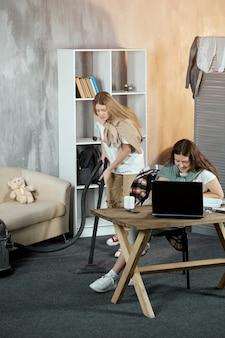 Een meisje zit aan een bureau en maakt huiswerk op een laptop, en haar vriend stofzuigt de kamer