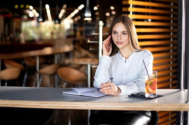 Een meisje zit aan een tafel in een café en schrijft een telefoongesprek in een notitieboekje