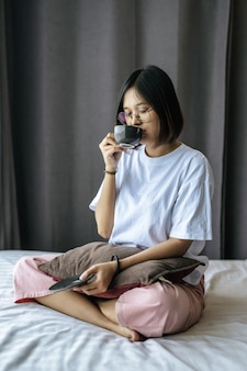 Een meisje zit en koffie drinken op de slaapkamer.
