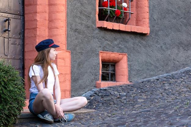 Een meisje zit in de buurt van een mooi huis en kijkt in de verte zichzelf fotograferend.