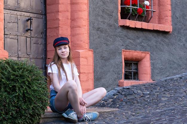 Een meisje zit in de buurt van een mooi huis en lacht zoet.