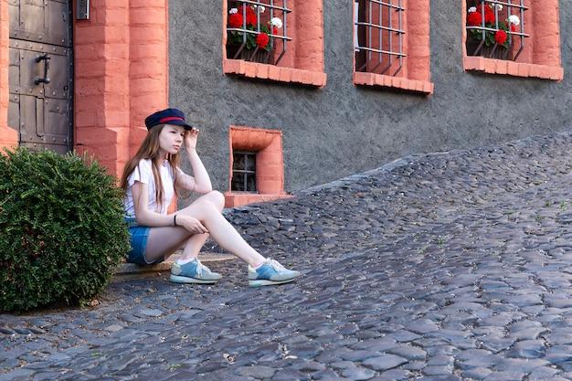 Een meisje zit in de buurt van een mooi huis en neemt foto's van zichzelf.