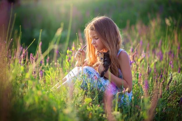 Een meisje zit in een bloeiend veld met een prachtig driekleurig kitten. bloeiende salie. een kat met een ongewone kleur voor een halve muilkorf