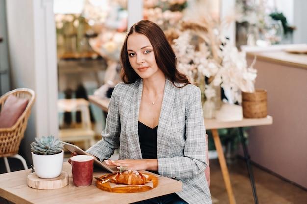 Een meisje zit in een café en kijkt naar een tablet, een meisje in een coffeeshop glimlacht, werk op afstand.