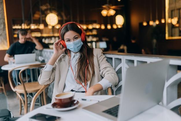 Een meisje zit in een coffeeshop met een uitbraak van coronavirus op een koptelefoon