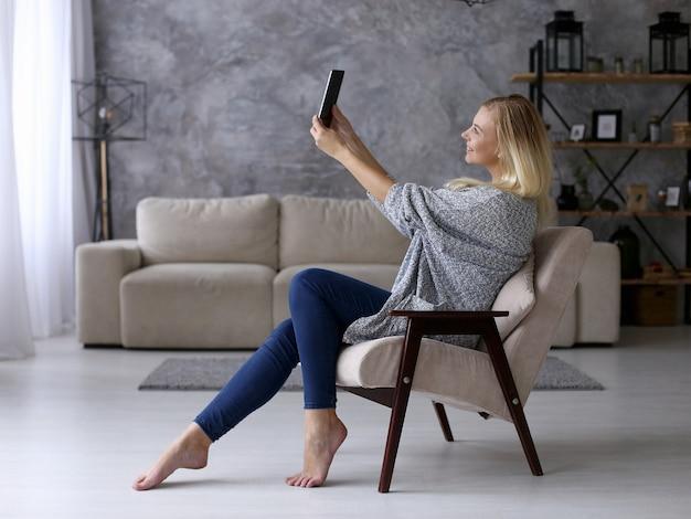 Een meisje zit in een stoel en neemt foto's op een tablet. werk comfortabel op afstand thuis via video. copyspace.