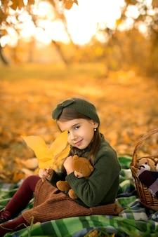 Een meisje zit op een deken in het park met een speelgoedbeer en bedekt haar oog met een droog herfstblad