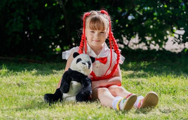 Een meisje zit op een open plek met een speelgoedpanda in de zomer in het park. hoge kwaliteit foto