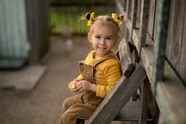 Een meisje zit op een oude houten ladder met een korenaar