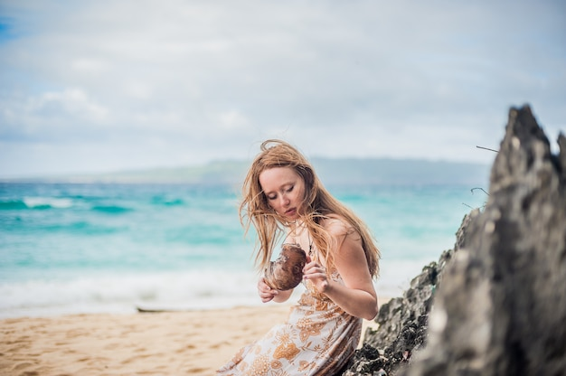 Een meisje zit op een rots op het strand van boracay