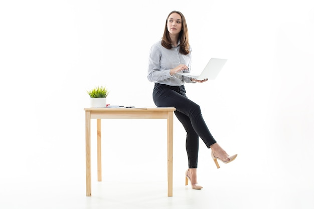 Een meisje zit op een tafel en typt op een computer op een witte achtergrond
