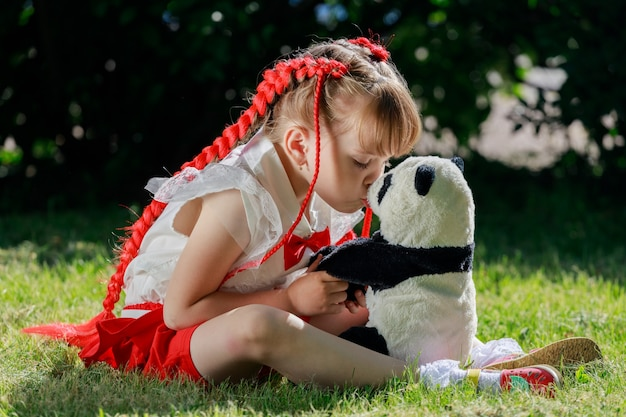 Een meisje zit op het gazon met een speelgoedpanda en kust hem op de neus. hoge kwaliteit foto