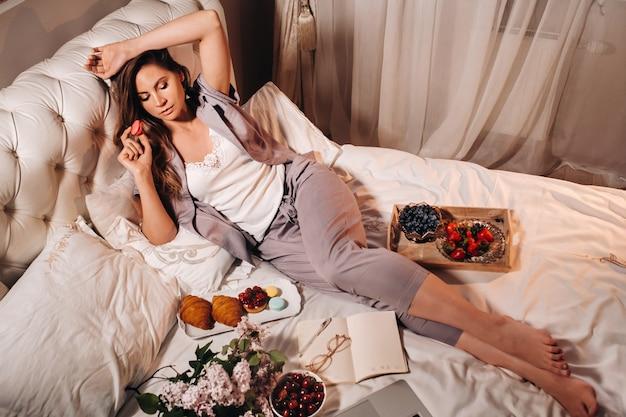 Een meisje zit 's avonds in bed en kijkt naar een laptop en eet aardbeien, een meisje in bed eet snoep voordat ze naar bed gaat