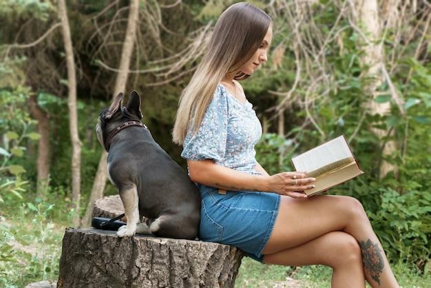 Een meisje zit zijdelings naar de kijker op een boomstronk en leest een boek waar een franse bulldog achter zit