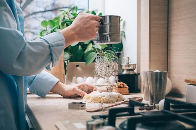 Een meisje zonder gezicht bereidt deeg, bestrooit het met bloem, close-up. zelfgemaakt gebak koken in de keuken, thuis. culinaire achtergrond.