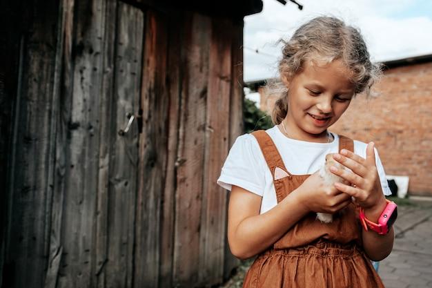 Een meisje zorgt voor de pasgeboren gele kippen in de tuin. klein huis boerderij en kinderboerderij concept