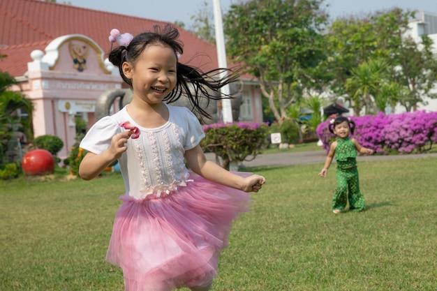 Een meisjes roze kleding die gelukkig in de tuin loopt speelt
