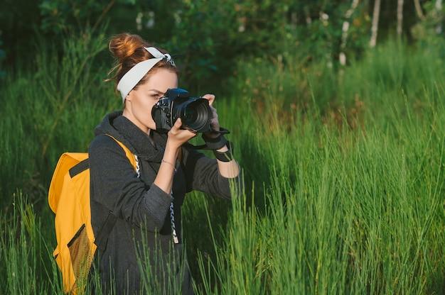 Een meisjesfotograaf houdt een professionele foto-videocamera in haar handen. tegen de achtergrond van prachtige groene natuur en bossen.