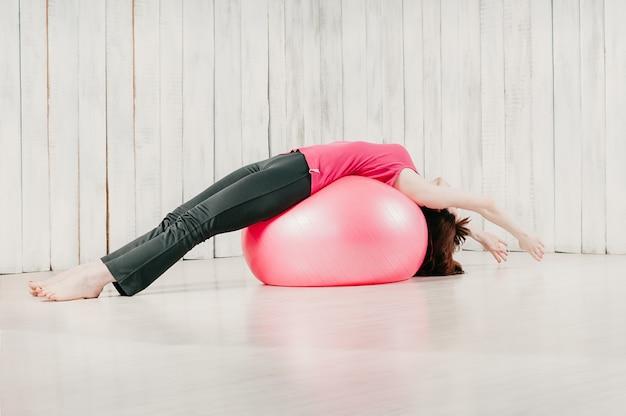 Een meisjesholding saldo het liggen stelt over een roze fitball in een gymnastiek