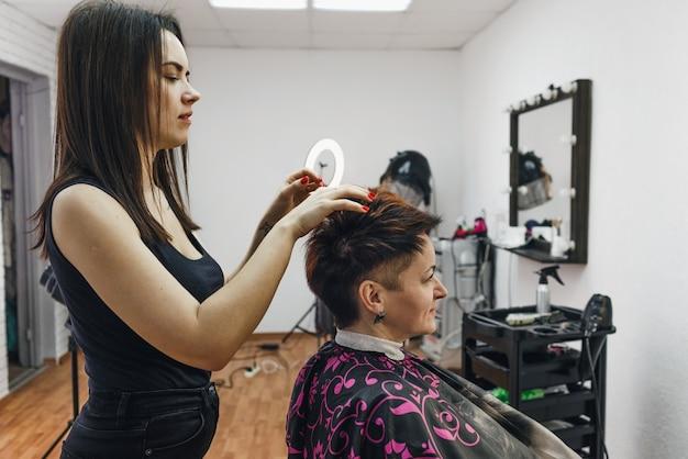 Een meisjeskapper maakt een kapsel voor een vrouwelijke cliënt in een moderne schoonheidssalon. de kunst van het kappersvak.