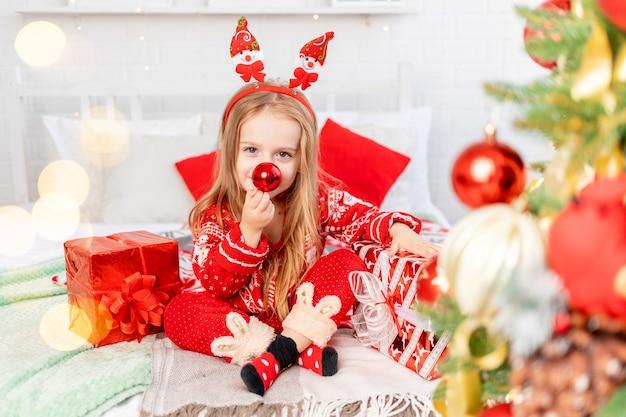 Een meisjeskind op het bed thuis is gek aan het maken van een neus uit een kerstbal en wacht op het nieuwe jaar of kerstmis in een rode kerstmanhoed en lacht van geluk