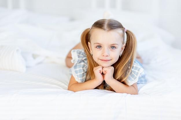 Een meisjeskind op het bed thuis op een wit katoenen bed ligt en glimlacht zoet.