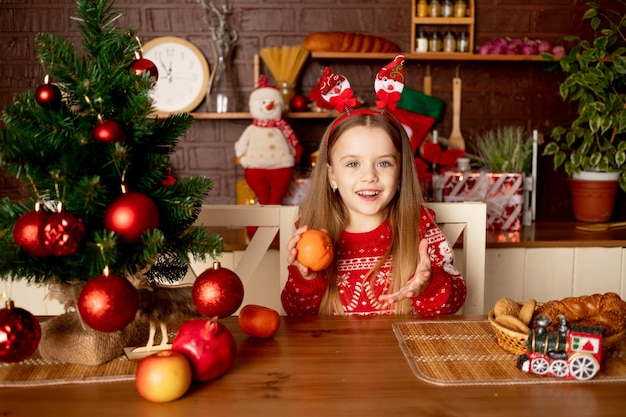 Een meisjeskind speelt of eet mandarijnen in een donkere keuken onder een kerstboom met rode ballen, het concept van nieuwjaar en kerstmis