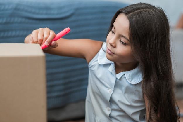 Een meisjestekening met viltpennen op een kartonnen doos