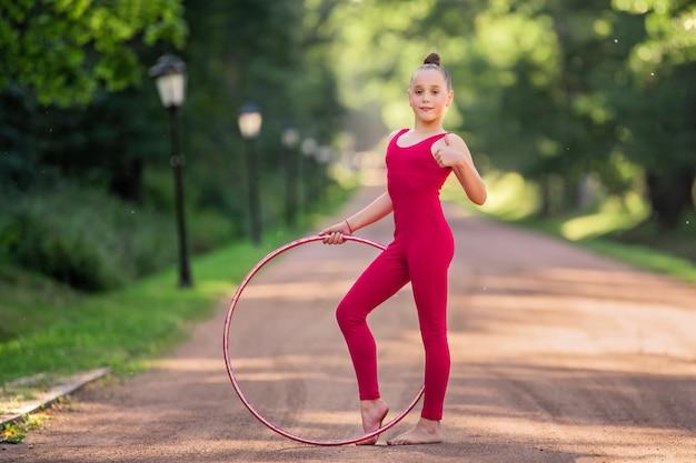 Een meisjesturner in een rood commando doet op een zomeravond een oefening met een hoepel in het park