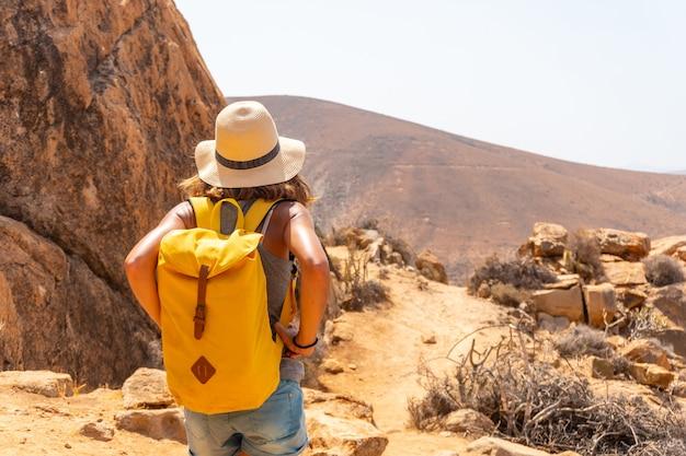 Een meisjeswandelaar met een gele rugzak op het mirador de la peñitas-pad in de peñitas-canyon, fuerteventura, canarische eilanden. spanje