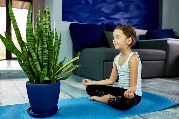 Een meisjeszitting in yogaasana op een blauw.