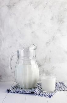 Een melkboer en een glas melk op een lichte tafel
