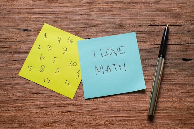 Een memo notities geschreven met cijfers en i love math op een houten bord