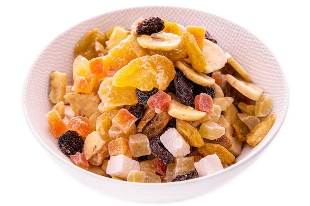 Een mengsel van gehakte gedroogde vruchten en bessen, noten in een witte schotel op een witte achtergrond. geïsoleerde artikelen en producten.