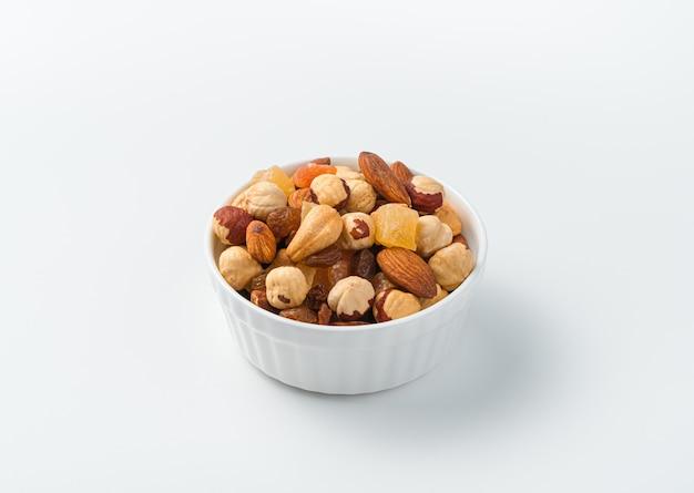 Een mengsel van noten en gedroogde vruchten in een witte kom op een lichte achtergrond