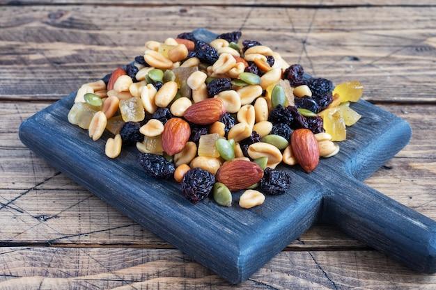 Een mengsel van noten en gedroogde vruchten op een houten snijplank, rustieke achtergrond. concept van gezonde voeding.