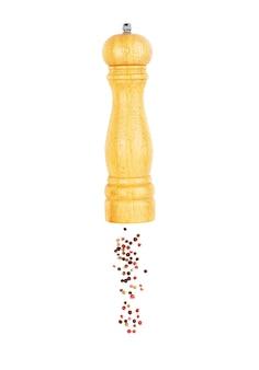 Een mengsel van paprika's die uit een houten peperschudbeker op een witte achtergrond gieten