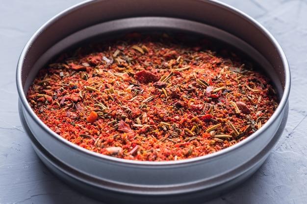 Een mengsel van verschillende kruiden in een pot close-up op een grijze achtergrond kruiden en specerijen