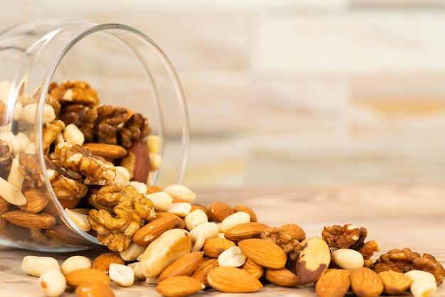 Een mengsel van verschillende noten wordt uit een glazen pot op tafel gegoten. noten als textuur en achtergrond, macro