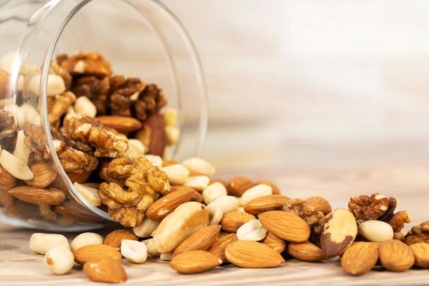 Een mengsel van verschillende noten wordt uit een glazen pot op tafel gegoten