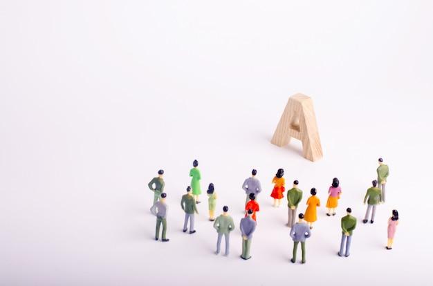 Een menigte mensen staat en kijkt naar de letter a